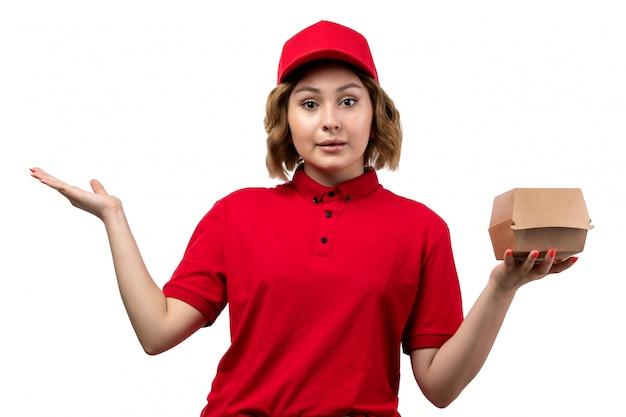 Une vue de face jeune femme ouvrière de messagerie de service de livraison de nourriture tenant le paquet de livraison de nourriture sur blanc