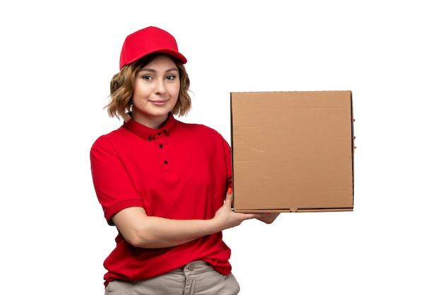Une vue de face jeune femme ouvrière de messagerie de service de livraison de nourriture tenant le paquet de livraison de nourriture souriant sur blanc