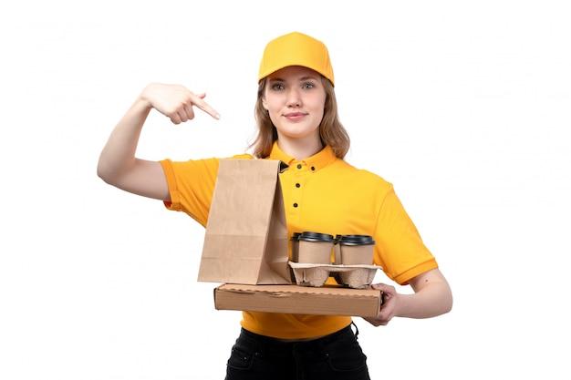 Une vue de face jeune femme ouvrière de messagerie de service de livraison de nourriture tenant des paquets de nourriture tasses de café et souriant sur blanc