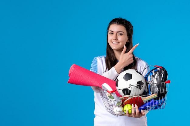 Vue de face jeune femme avec panier après le sport shopping sur mur bleu