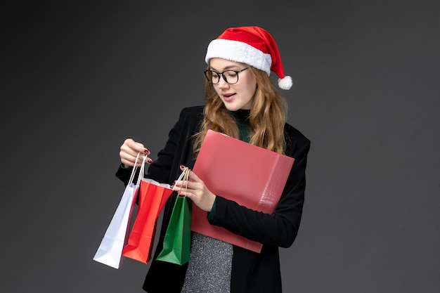 Vue de face jeune femme avec des paquets sur le mur sombre cadeau cadeaux de noël du nouvel an