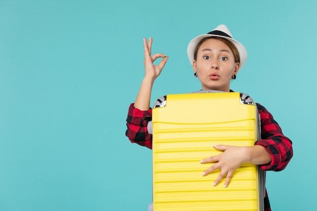 Vue de face jeune femme partant en vacances avec son gros sac sur un bureau bleu