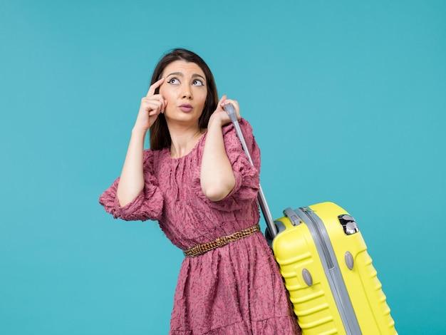 Vue de face jeune femme partant en vacances avec son gros sac sur le fond bleu voyage été voyage femme mer humaine
