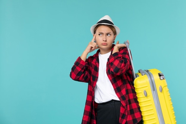 Vue de face jeune femme partant en vacances avec son sac jaune sur un bureau bleu