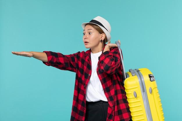 Vue de face jeune femme partant en vacances avec son sac jaune sur l'espace bleu