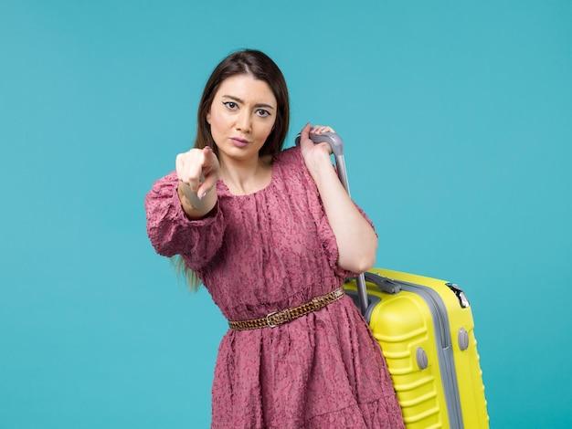 Vue de face jeune femme partant en vacances avec son sac jaune sur le fond bleu voyage été voyage femme mer humaine