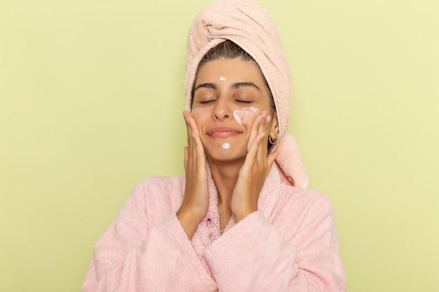 Vue de face jeune femme en peignoir rose appliquant la crème pour le visage sur une surface vert clair