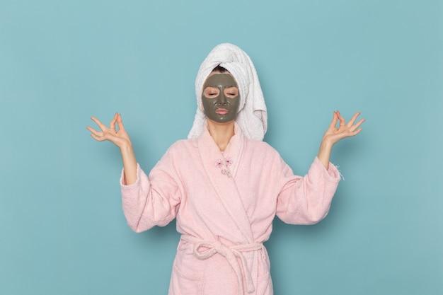 Vue de face jeune femme en peignoir rose après la douche sur le bureau bleu crème de bain d'eau de beauté douche auto-soins salle de bains