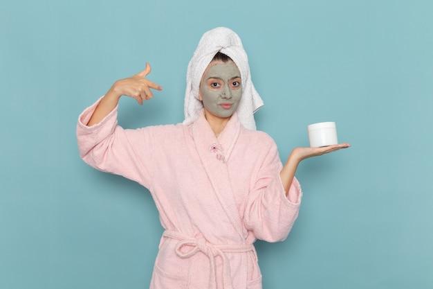 Vue de face jeune femme en peignoir rose après la douche avec masque sur son visage tenant la crème sur le mur bleu douche nettoyage beauté crème auto-soin