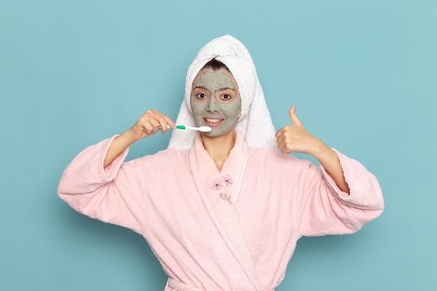 Vue de face jeune femme en peignoir rose après douche nettoyage des dents sur le mur bleu clair de l'eau de beauté douche propre