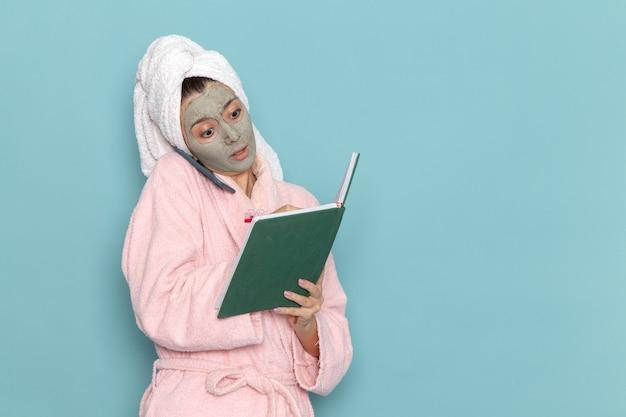 Vue de face jeune femme en peignoir rose après la douche parler au téléphone de lecture de cahier sur mur bleu clair eau de beauté douche propre