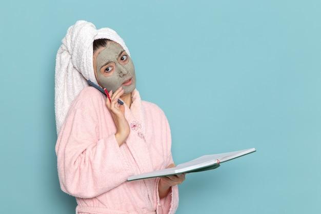 Vue de face jeune femme en peignoir rose après la douche, parler au téléphone sur le mur bleu crème de l'eau de beauté douche selfcare
