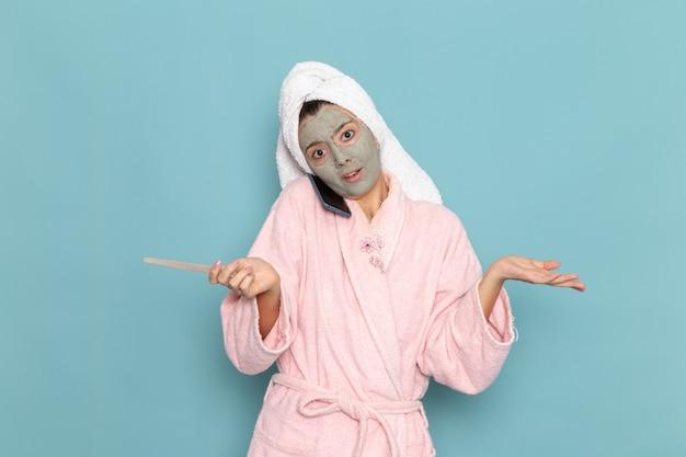 Vue de face jeune femme en peignoir rose après la douche parler au téléphone sur le mur bleu de l'eau de beauté propre douche propre