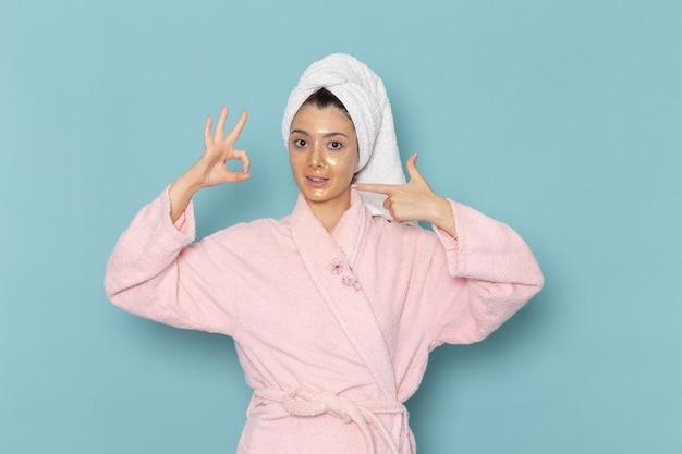 Vue de face jeune femme en peignoir rose après la douche posant juste sur le mur bleu nettoyage beauté eau propre crème douche