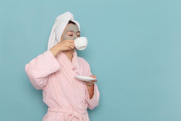 Vue de face jeune femme en peignoir rose boire du café sur le mur bleu nettoyage beauté eau propre crème douche