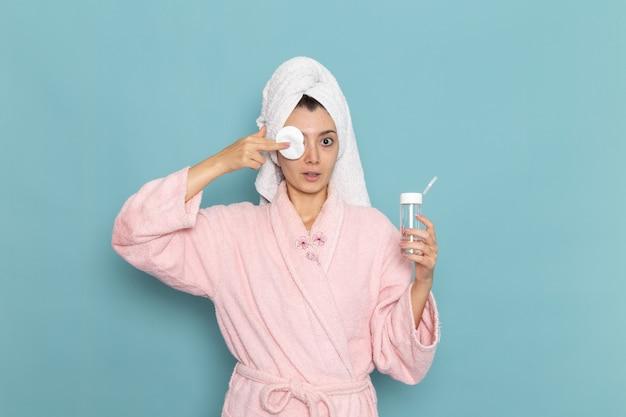 Vue de face jeune femme en peignoir rose nettoyant son visage de maquillage sur le bureau bleu nettoyage douche selfcare