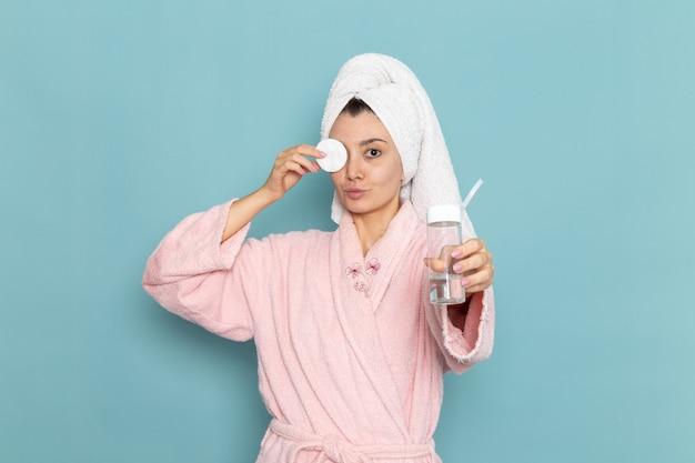 Vue de face jeune femme en peignoir rose nettoyer son visage de maquillage sur le mur bleu douche nettoyage beauté crème auto-soin