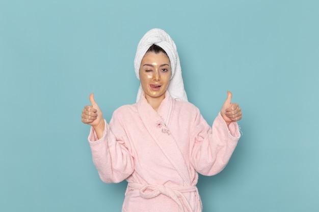 Vue de face jeune femme en peignoir rose posant sur le mur bleu douche nettoyage beauté crème auto-soins