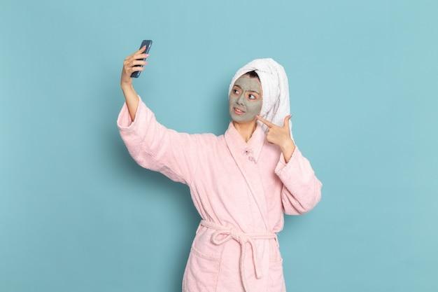 Vue de face jeune femme en peignoir rose prenant selfie avec masque sur son visage sur le bureau bleu nettoyage douche crème auto-soin