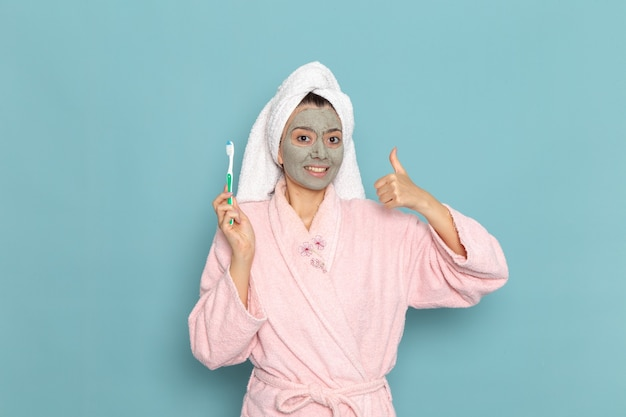 Vue de face jeune femme en peignoir rose tenant la brosse à dents sur le mur bleu nettoyage beauté eau propre douche crème auto-soins
