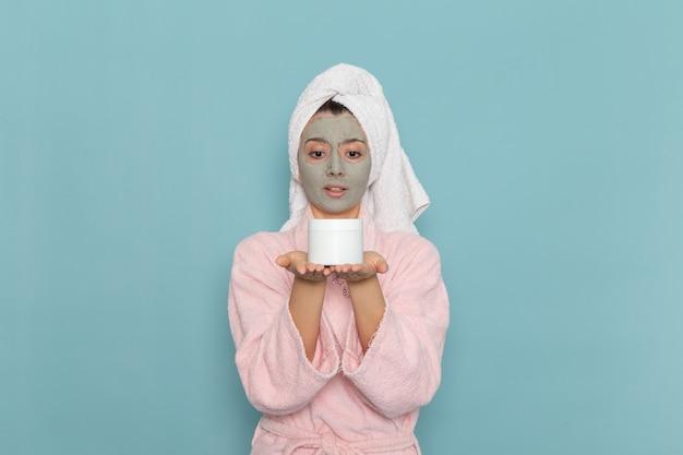 Vue de face jeune femme en peignoir rose tenant la crème sur le mur bleu clair douche nettoyage beauté crème auto-soins