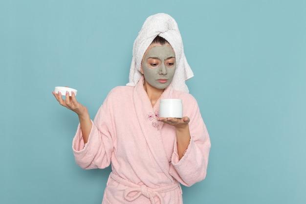 Vue de face jeune femme en peignoir rose tenant la crème peut sur le mur bleu douche nettoyage crème auto-soin de beauté