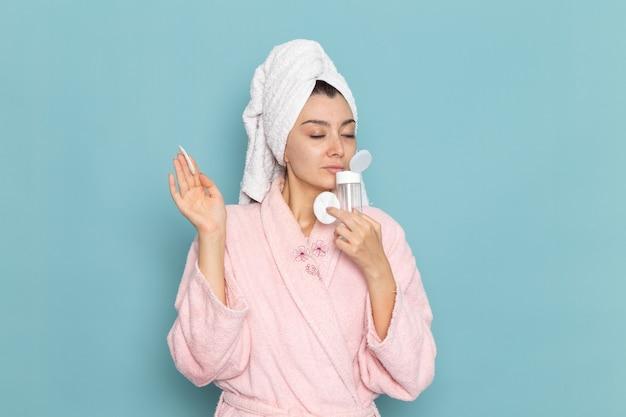 Vue de face jeune femme en peignoir rose tenant le démaquillant sur le mur bleu nettoyage beauté eau propre douche crème auto-soin