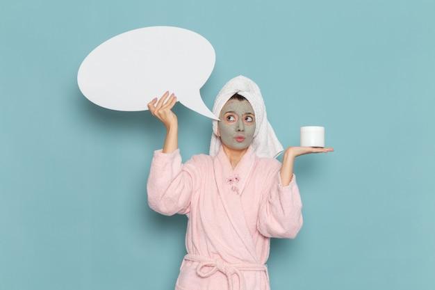 Vue de face jeune femme en peignoir rose tenant un énorme panneau blanc sur le mur bleu douche nettoyage beauté crème auto-soins