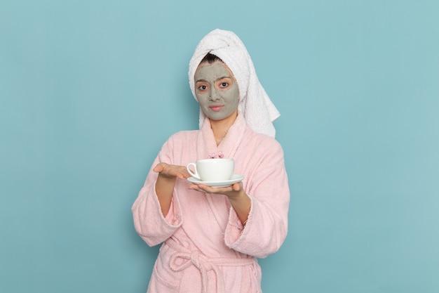 Vue de face jeune femme en peignoir rose tenant une tasse de café sur le mur bleu nettoyage douche crème auto-soin