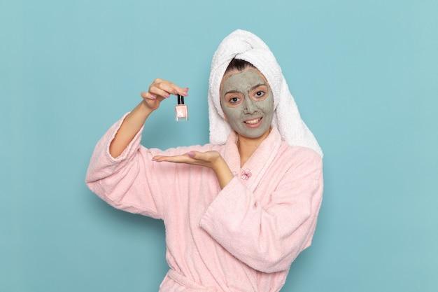 Vue de face jeune femme en peignoir rose tenant le vernis à ongles sur le mur bleu nettoyage beauté eau propre douche crème auto-soin