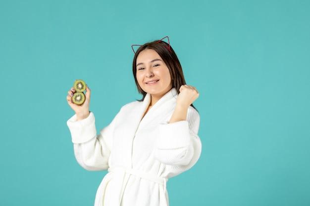 Vue de face jeune femme en peignoir tenant des kiwis tranchés et se réjouissant sur fond bleu