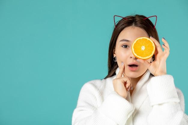 Vue de face jeune femme en peignoir tenant une tranche d'orange sur fond bleu