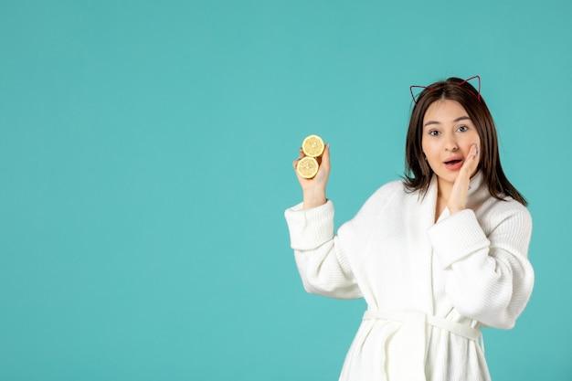Vue de face jeune femme en peignoir tenant des tranches de citron sur fond bleu