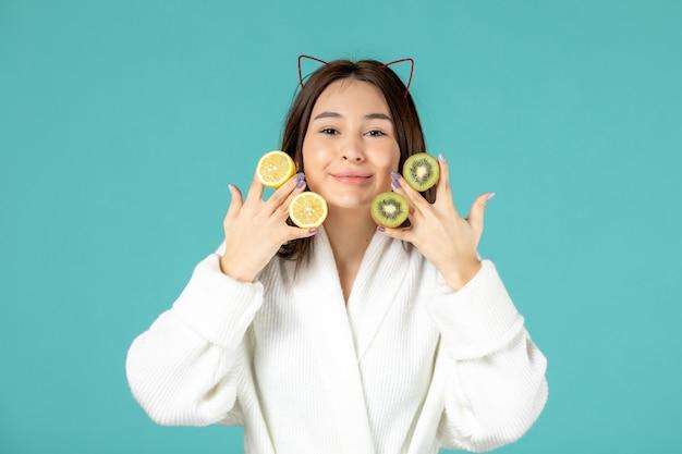 Vue de face jeune femme en peignoir tenant des tranches de citrons et de kiwis sur fond bleu