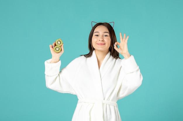 Vue de face jeune femme en peignoir tenant des tranches de kiwis sur fond bleu