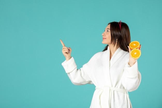 Vue de face jeune femme en peignoir tenant des tranches d'orange sur fond bleu