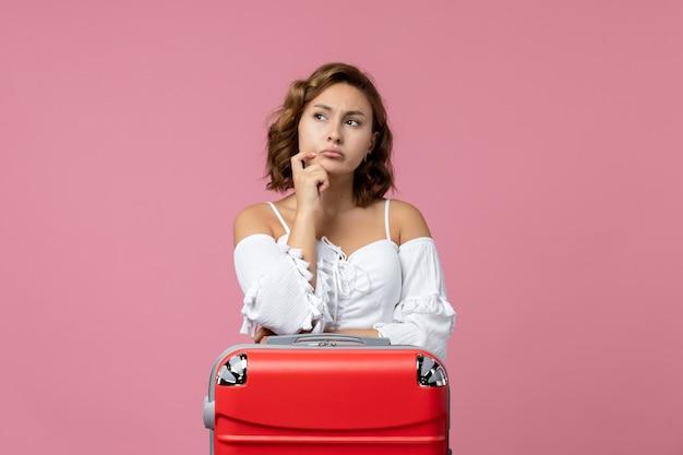 Vue de face d'une jeune femme pensant avec un sac de vacances rouge sur un mur rose
