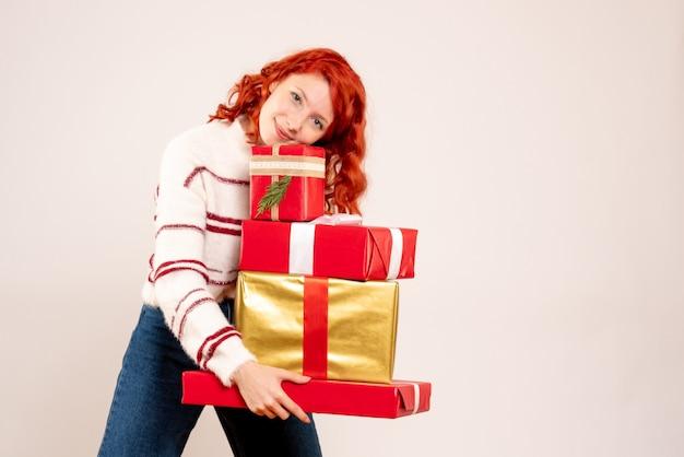 Vue de face de la jeune femme portant des cadeaux de noël sur un mur blanc