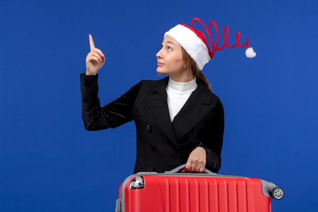 Vue de face jeune femme portant gros sac rouge sur mur bleu vacances voyage vacances femme