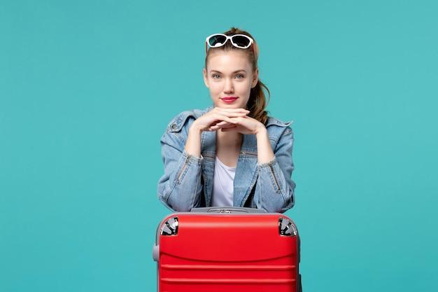 Vue de face jeune femme portant ses lunettes de soleil et se préparant pour des vacances sur l'espace bleu