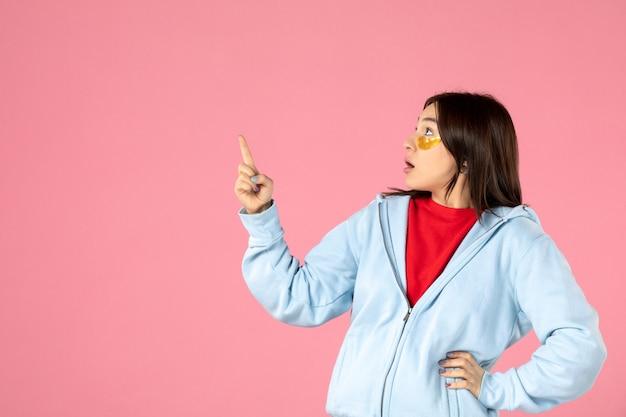 Vue de face d'une jeune femme posant avec des cache-œil sous ses yeux sur un mur rose