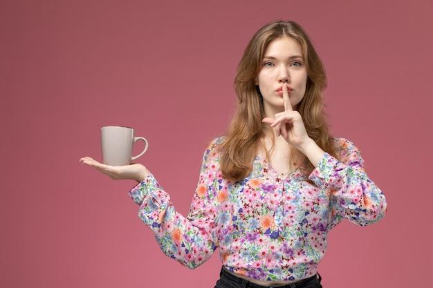 Vue de face jeune femme posant le geste de silence avec tasse