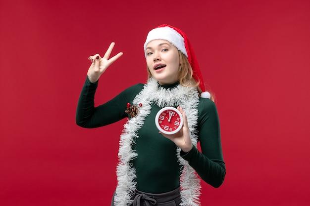 Vue de face jeune femme posant avec horloge sur fond rouge