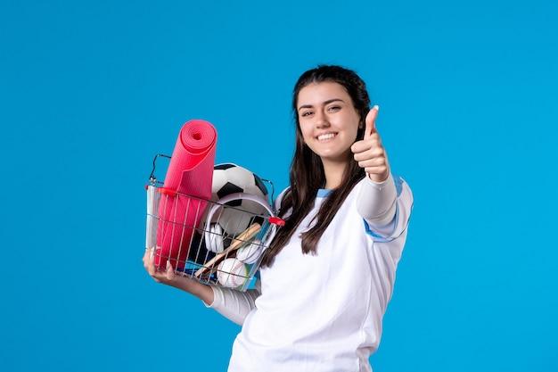 Vue de face jeune femme posant avec panier après le sport shopping mur bleu