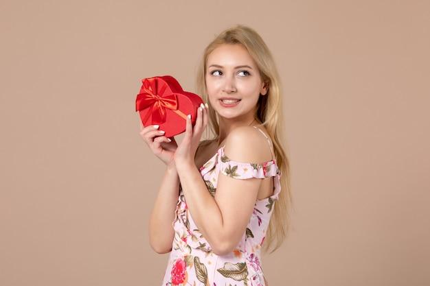 Vue de face d'une jeune femme posant avec un présent en forme de coeur rouge sur un mur marron