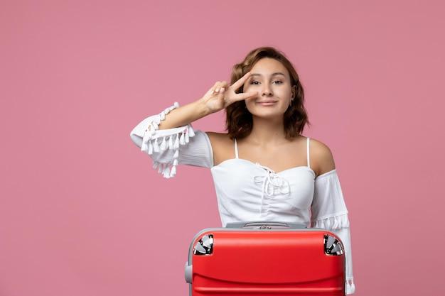 Vue de face d'une jeune femme posant avec un sac rouge sur un mur rose