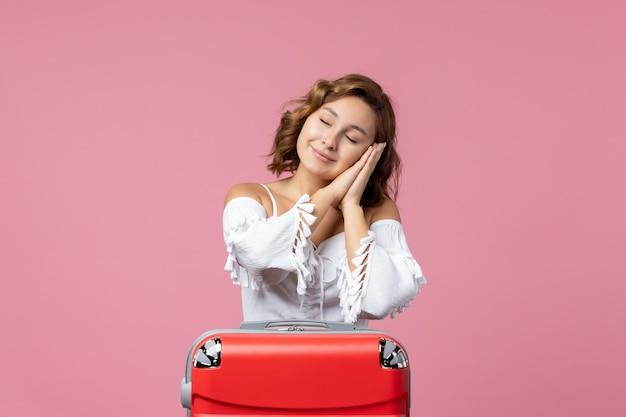 Vue de face d'une jeune femme posant avec un sac de vacances rouge sur le mur rose