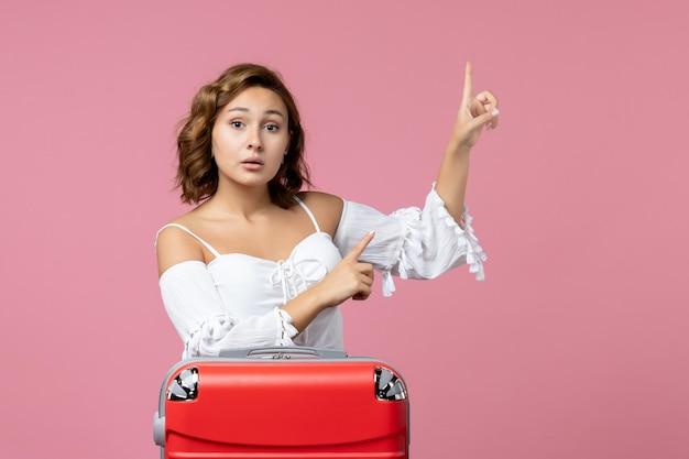Vue de face d'une jeune femme posant avec un sac de vacances rouge sur un sol rose modèle de voyage de vacances couleur de la mer