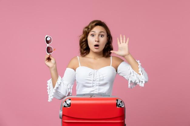 Vue de face d'une jeune femme posant et se préparant pour un voyage avec un sac rouge sur un mur rose clair