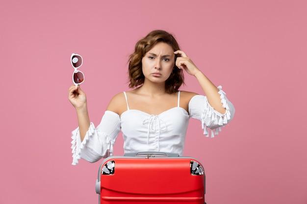 Vue de face d'une jeune femme posant et se préparant pour un voyage avec un sac rouge sur le mur rose